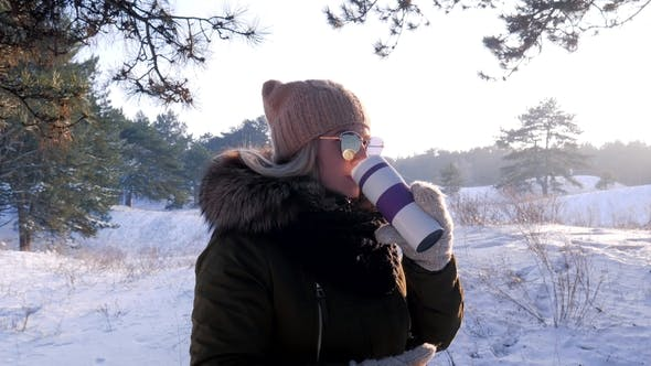 Cover Image for Beautiful Girl Is Enjoying Winter in Forest with a Mug of Warm Drink Outdoors