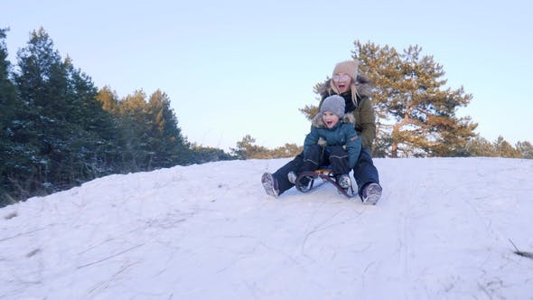 Thumbnail for Mother and Son with Open Mouths Ride on Sleigh from Snowy Hill in Winter Forest