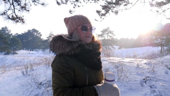Thumbnail for Cute Girl in Sunglasses Holds Cup with Hot Drink in Winter Day Outdoors at Snow Forest