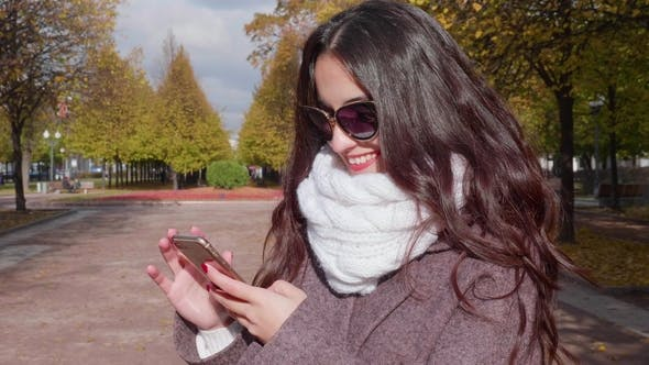 Thumbnail for Young Smiling Brunette Woman with Curled Long Hairs in Sunglasses Is Using Smartphone in Urban Park