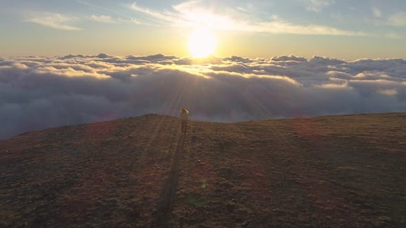 Thumbnail for Young Woman Is Walking to the Edge of Mountain Plateau Above Pink Clouds at Sunrise