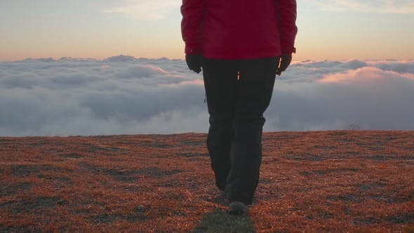 Thumbnail for Young Woman in Jacket and Pants Is Walking To the Edge of Mountain Plateau Above Clouds at Sunrise