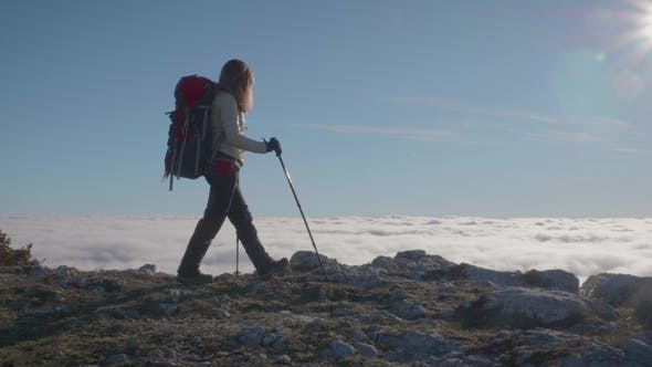 Cover Image for Young Woman with Backpack and Trekking Poles Is Hiking on the Edge of Mountain above the Clouds