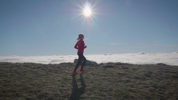 Cover Image for Young Woman Is Jogging in Mountains Above Clouds at Sunny Day. Sky Running