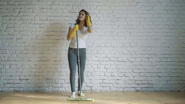 Beautiful Young Woman in Protective Gloves Is Singing Using a Mop and Dancing While Cleaning