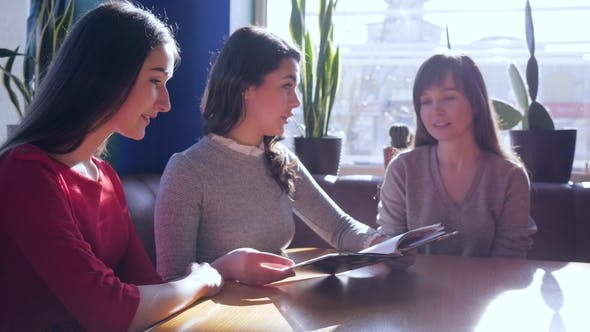 Cover Image for Female Company Looking at Menu Sitting at Table in Cafe