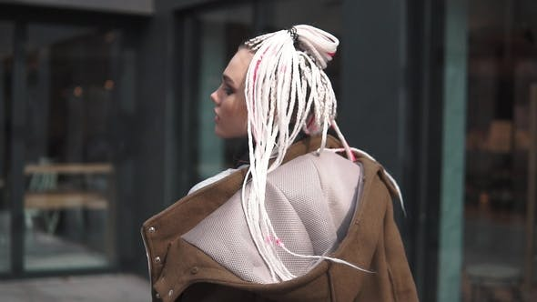 Thumbnail for Girl with an Unusual Appearance on the Background of Urban Architecture. Teenager with Dreadlocks