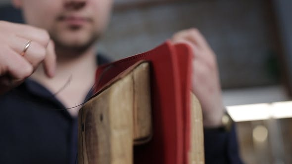 Man Creates a Brown Leather Wallet with His Own Hands with a Needle in the Leather Workshop,