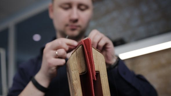 Thumbnail for Man Creates a Brown Leather Wallet with His Own Hands with a Needle in the Leather Workshop