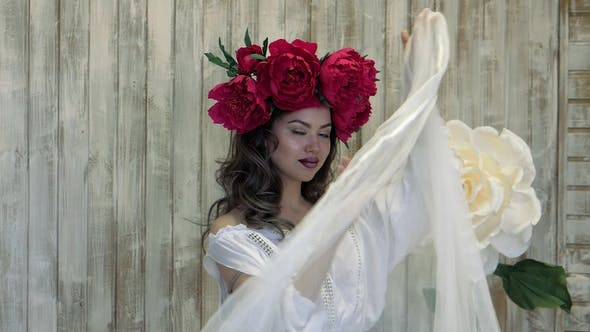 Thumbnail for Girl Posing in Front of Camera. Young Woman in a Wreath of Scarlet Peonies on Her Head, Dark Long