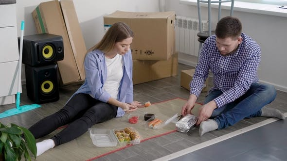 Thumbnail for Tired New Settlers Man and Woman Are Eating Sushi and Rolls Sitting on a Floor of Their New