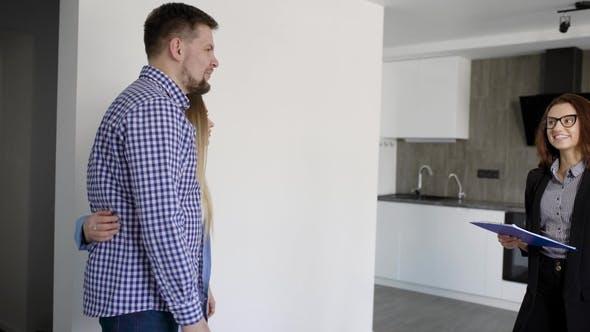 Thumbnail for Immobilienmakler Frau zeigt neue Wohnung zu jungen Ehepaar, Betreten in ein Wohnzimmer mit