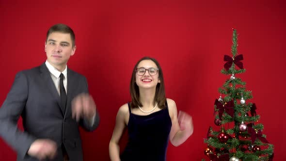 Thumbnail for Young Man and Woman Dancing Near the Christmas Tree. A Man in a Suit and a Woman in a Dress on a Red