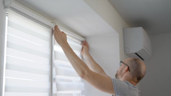Thumbnail for Adult Man Is Installing a Rod for Blinds on a Window Frame in a Living Room in Daytime and Fixing