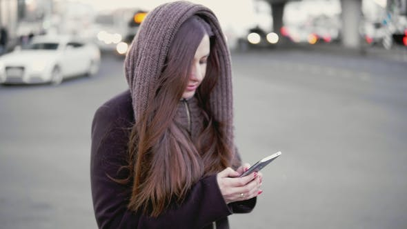 Thumbnail for Young Woman Uses a Smartphone in the City