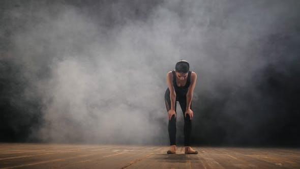 Thumbnail for Young Beautiful Tired Ballerina in Black Suit Stands on Stage with Smoke After the Performance. The