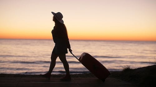 Exotic Vacation Silhouette of Female Pulling Travel Suitcase on Seafront Alley Luminous Sunrise