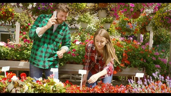 Thumbnail for Content Couple Working in Floral Garden
