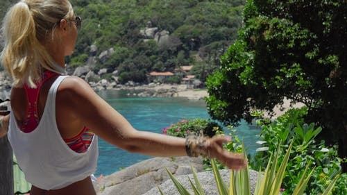 Tanned Sporty Female Meditating in Front of Gorgeous Tanote Bay on Sunny Day. Light Ocean Breeze