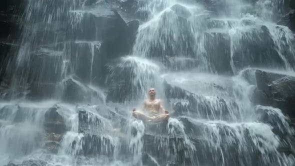 Thumbnail for Man Sitting in Yoga Pose at Background Waterfall