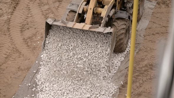 Thumbnail for a Close Shot on a Metal Ladle, Heavy Machinery Unloads Small Stones, Pebbles on the Road, in Order