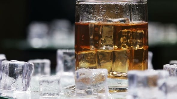 Thumbnail for Whiskey in a Glass of Ice on a Black Background
