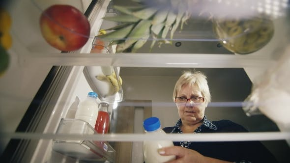 Thumbnail for An Senior Woman Takes a Bottle of Milk From the Refrigerator, Checks the Shelf Life of the Product