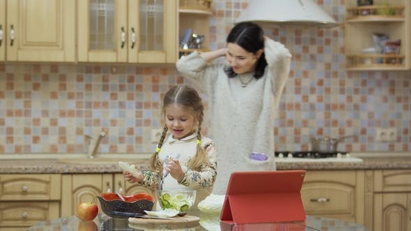 Thumbnail for Mother Looks at Her Little Daughter Mix Fresh Salad in a Bowl