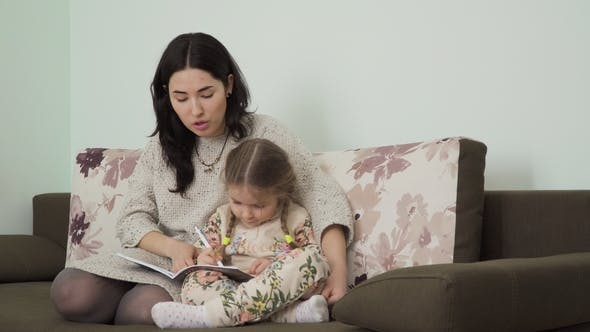 Thumbnail for Young Woman Helps Her Daughter To Make Homework