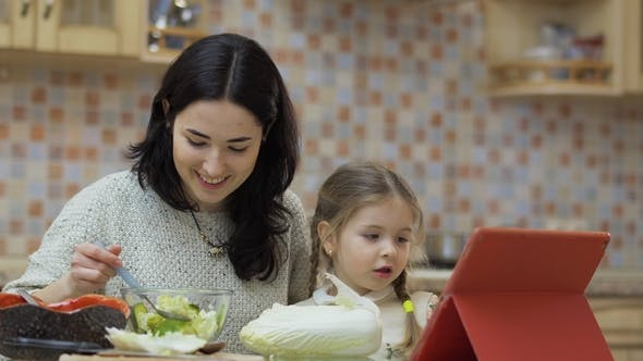 Thumbnail for Young Mother Sits with Little Daughter on the Kitchen