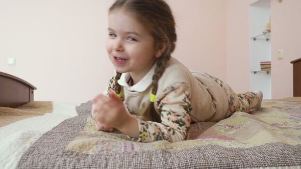 Thumbnail for Adorable Little Girl with Pigtails Relaxing on the Bed at Home