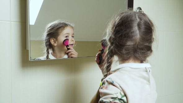 Thumbnail for Cute Little Girl Applies Powder on Her Face with Brush in Front of Mirror