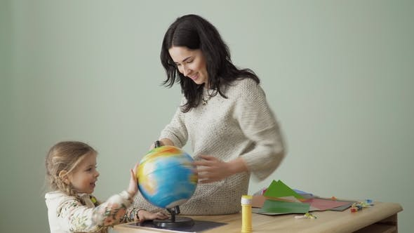 Thumbnail for Young Mother and Little Daughter Spins the Globe on Table