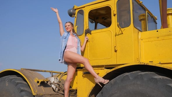 Thumbnail for Young Woman in High-heeled Shoes Waving of Hand and Smiling While Standing on Big Tractor Wheel