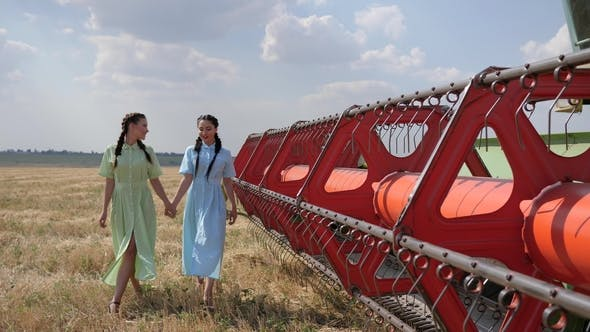 Thumbnail for Two Rural Females in Dress Holding Hands together near Red Agricultural Machine