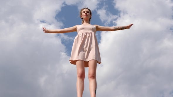 Cover Image for Beautiful Girl in Short Dress Raises Hands up on Blue Sky Background