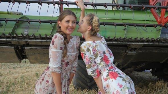Thumbnail for Rural Girls in Dress Whispering Gossips of Girlfriends in Ear on Field near Combine Harvester