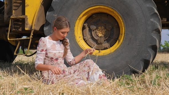 Cover Image for Pretty Young Woman in Dress Sits near Big Wheel of Combine-harvester on Rural Farm