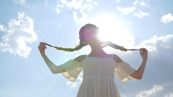 Cover Image for Cute Girl in White Dress with Braid Hair in Backlight on Background of Blue Heaven