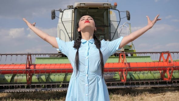 Thumbnail for Sexy Young Woman in Dress Raises Hands up on Agricultural Machinery Background