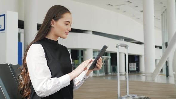 Thumbnail for Young Female Passenger at the Airport, Using Her Tablet Computer While Waiting for Her Flight