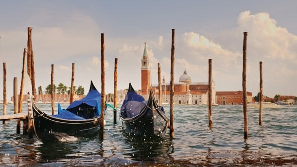 Thumbnail for Two Gondolas at the Pier Against the Backdrop of the Coastline of Venice, Italy. In the Foreground