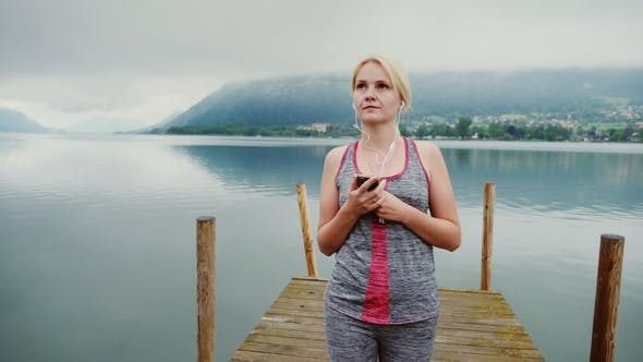 Thumbnail for A Woman Walks Along a Wooden Pier in the Background of a Mountain Lake in the Austrian Alps. Listens