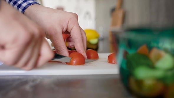Thumbnail for Crop Unrecognizable Man Standing at Table on Kitchen and Chopping Tomato on Cutting Board