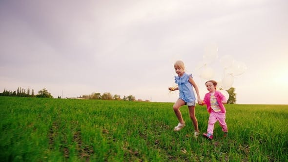 Thumbnail for Two Carefree Girls Run Across the Green Meadow, Holding Hands. They Rejoice in the Arrival of Spring