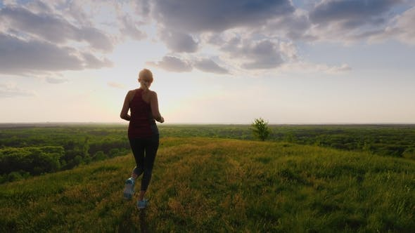 Cover Image for A Run in a Picturesque Place at Sunset. A Woman Runs Towards the Sun, a Back View