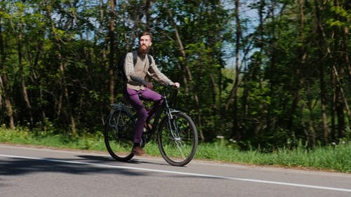A Man with a Beard Is Riding a Bicycle. Against the Background of a Green Forest - Ecotourism, an