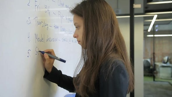 Thumbnail for Woman in an Office on Blackboard By Marker Writing Text in English.