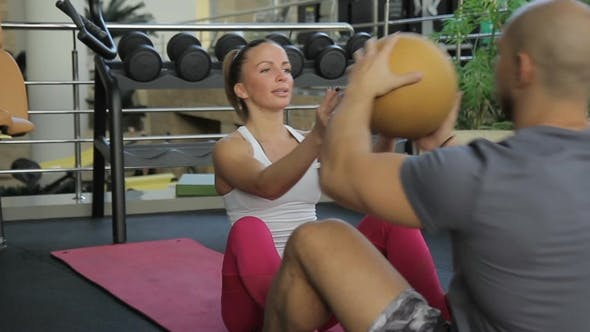 Thumbnail for The Couple Does Sit-ups on the Pink Mats During the Training in the Modern Gym.