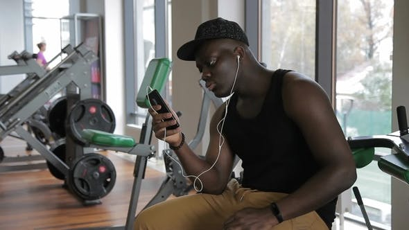Thumbnail for African Man in Gym Sits and Listens To Music Through Headphones of Phone.